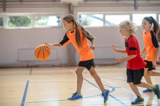 Sportzeit. kinder in heller sportbekleidung spielen zusammen basketball und fühlen sich energetisiert