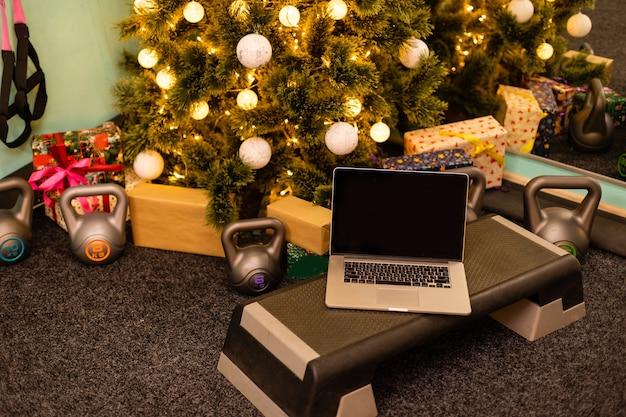 Sportzubehör. hanteln, computertablette, tannenzweige und weihnachtsdekorationen im hintergrund. draufsicht mit kopienraum. fitness, sport und gesunder lebensstil.