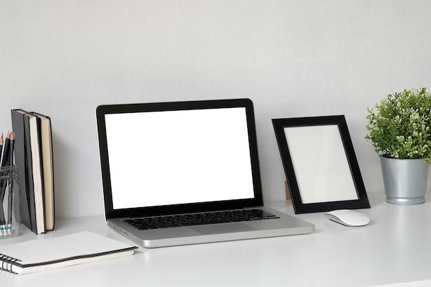 Spott herauf laptop auf arbeitsraum mit fotorahmen, plattform und glas des bleistiftkopienraumbüros.