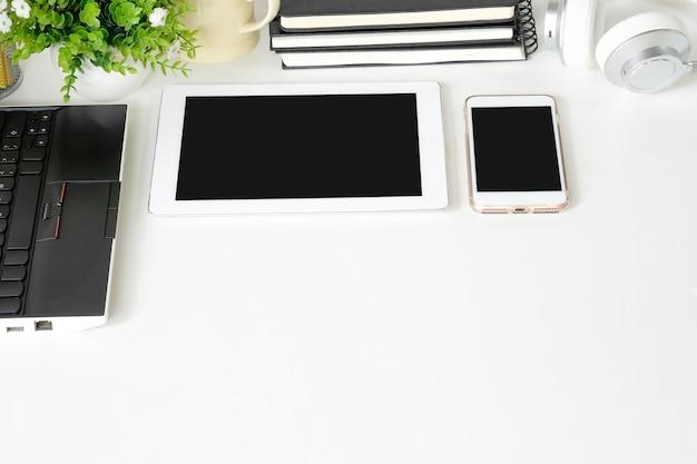 Spott herauf smartphone und tablette mit laptop-computer auf arbeitsplatzbüro.