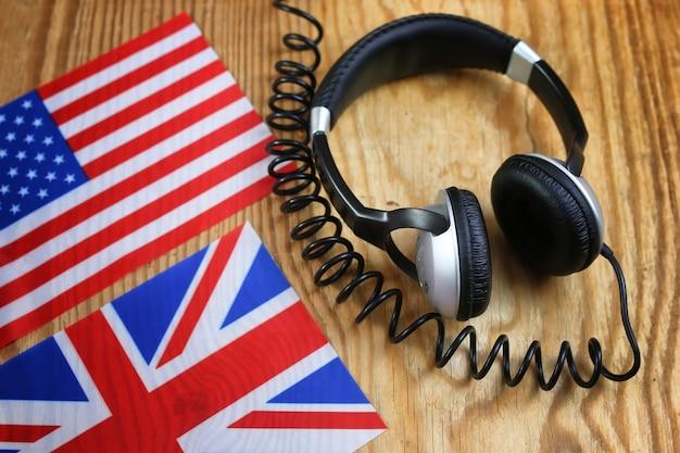 Sprachkurs kopfhörer und flagge auf holztisch