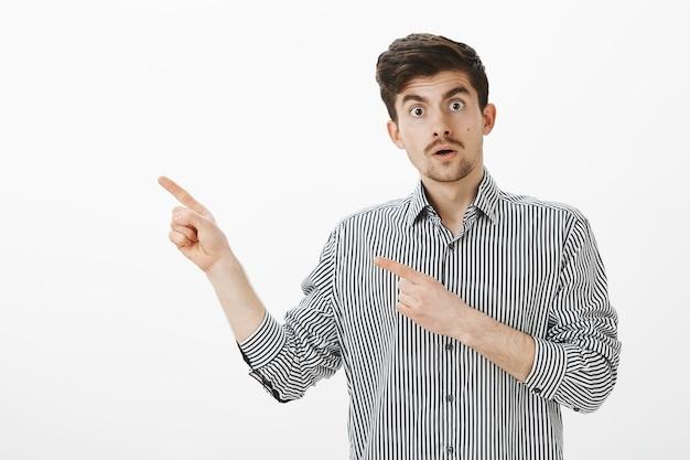 Sprachlos schockierter attraktiver kerl mit schnurrbart, der auf die obere linke ecke zeigt und den kiefer fallen lässt und über einen unglaublichen unfall spricht, der fassungslos und erstaunt ist