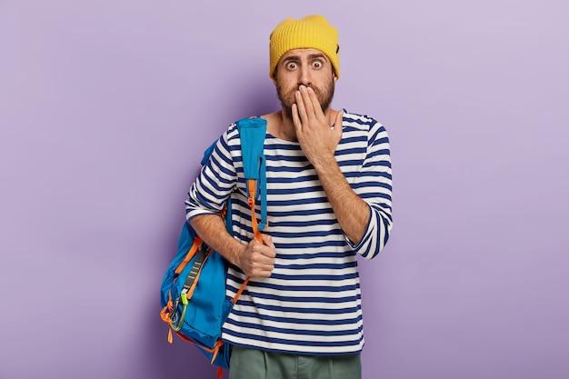 Sprachloser emotionaler backpacker hält handfläche auf mund, traut augen nicht, hat aktiven lebensstil