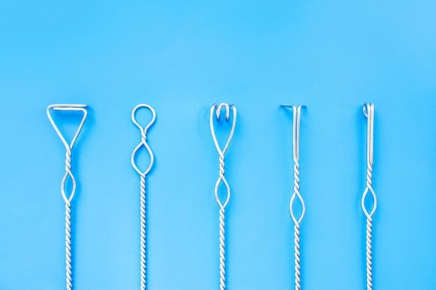 Sprachtherapiewerkzeuge auf einem blauen hintergrund. logopädische metallsonden. sprachkorrektur