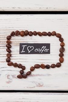 Sprechblase aus kaffeebohnen mit i love coffee message. weiße holzoberfläche.
