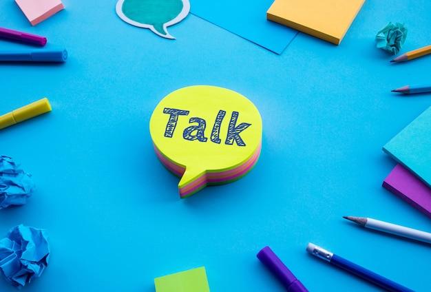 Sprechen sie text auf chat, sprechblasenpapier auf blauem tabellenfarbhintergrund