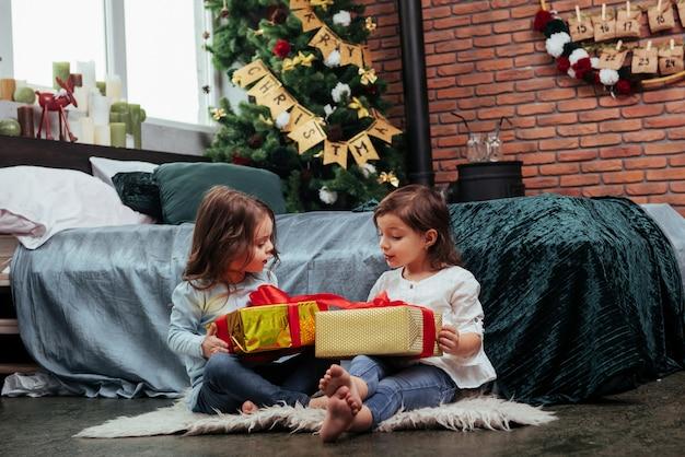 Sprechen, während bunte kästen gehalten werden. weihnachtsferien mit geschenken für diese beiden kinder, die drinnen im schönen raum neben dem bett sitzen