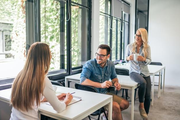 Sprechen während der arbeit im gemeinsamen arbeitsraum. drei leute, die auf trainingsklasse sprechen.