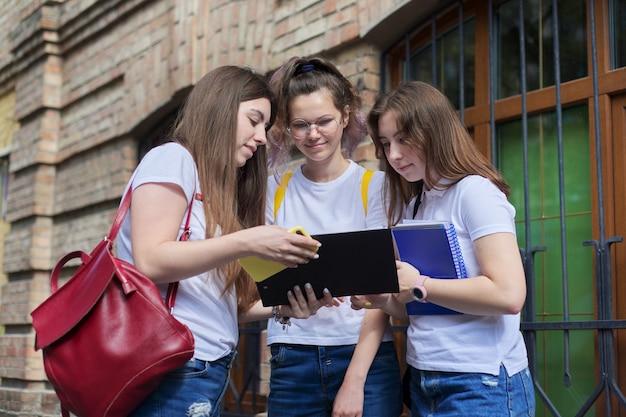 Sprechende gruppe von studentinnen, college-studenten im teenageralter in der nähe des backsteingebäudes. zurück zum college, beginn des unterrichts, ausbildung, high school