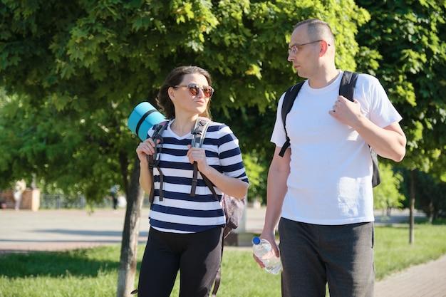 Sprechender mann und frau mittleren alters, paar, das entlang der parkstraße für sportfitness-training geht