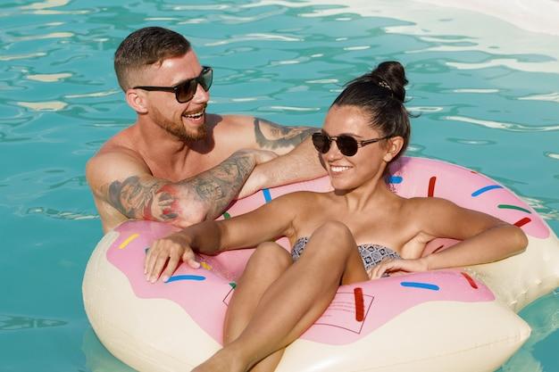 Sprechendes glückliches paar beim schwimmen auf aufblasbarem donut am pool