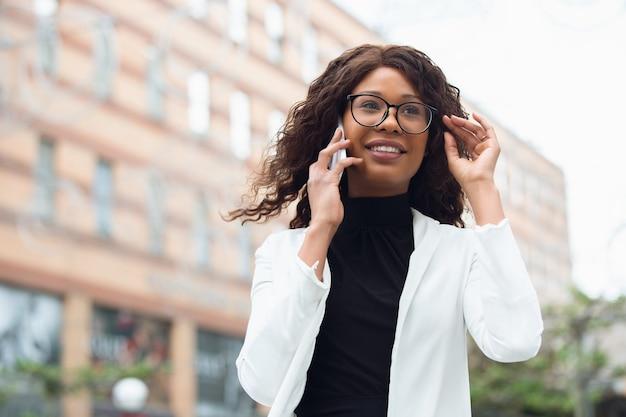 Sprechendes telefon. afroamerikanische geschäftsfrau in bürokleidung lächelnd, sieht selbstbewusst und ernst aus, beschäftigt. konzept für finanzen, wirtschaft, gleichstellung und menschenrechte. schönes junges modell, erfolgreich.