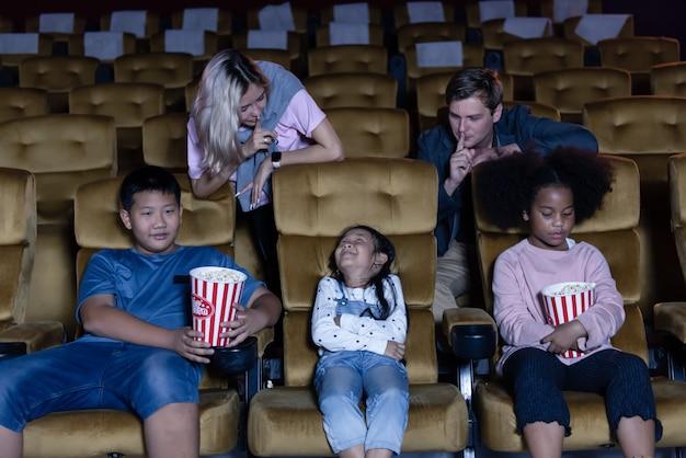 Sprechendes und spielendes kind beim aufpassen des films im theater.