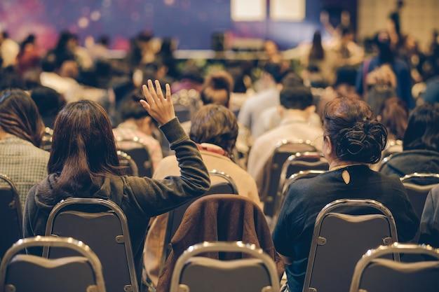 Sprecher auf der bühne mit hinterer ansicht des publikums in gesetztem hand up acton