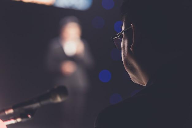 Sprecher, der ein gespräch auf unternehmensgeschäfts-konferenzsaal- oder seminarraumhintergrund gibt.