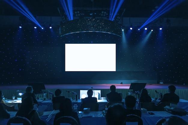 Sprecher, der einen vortrag auf unternehmensgeschäfts-konferenzhallen- oder -seminarraumhintergrund gibt.