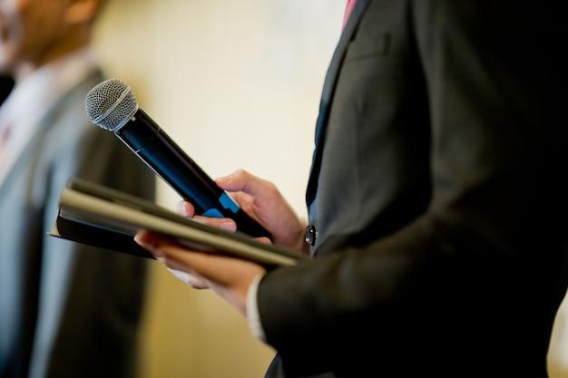 Sprecher mit mikrofon auf der bühne, konferenz