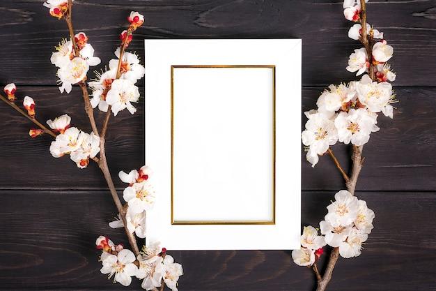 Sprigs des aprikosenbaums mit blumen und weißem fotorahmen auf hölzernem hintergrund.
