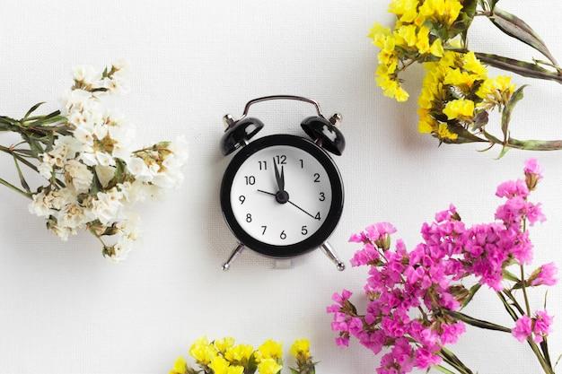 Spring time change mit wecker und blumenzweigen