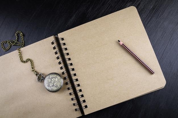Springbinding gelbes papier geöffnete notebook-taschenuhr mit kette und bleistift darauf flach legen