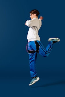 Springen. altmodischer junger mann, der lokalisiert auf blauem studio tanzt