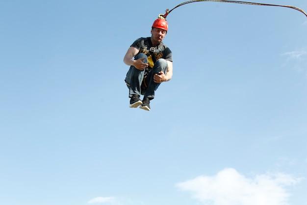 Springen mit einem seil extremer mann, der aus großer höhe springt. beteiligen sie sich am seilspringen