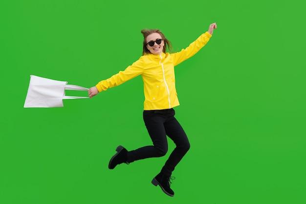 Springende frau mit sonnenbrille mit öko-tasche in der hand isoliert auf grünem hintergrund