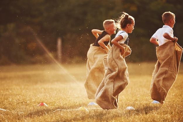 Springende sackhüpfen im freien im feld. kinder haben spaß am sonnigen tag. Premium Fotos
