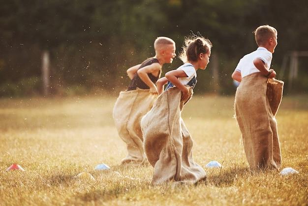 Springende sackhüpfen im freien im feld. kinder haben spaß am sonnigen tag.