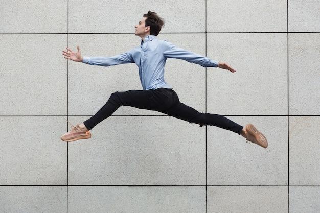 Springender büromann in der stadt, balletttänzerin