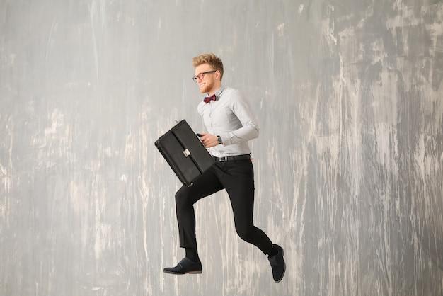 Springender geschäftsmann mit stilvoller aktentasche auf grau