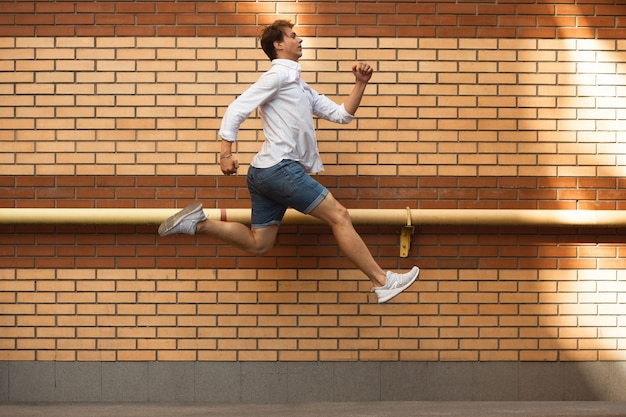 Springender junger geschäftsmann vor gebäuden, auf der flucht in hochsprung