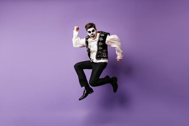 Springender lachender mann im halloween-kostüm. innenfoto des aufgeregten kerls mit mexikanischem make-up, das auf lila wand tanzt.
