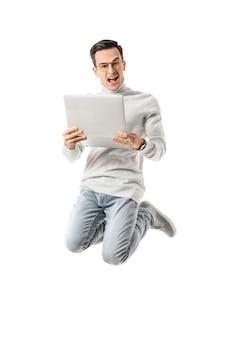 Springender mann mit laptop auf weißer oberfläche