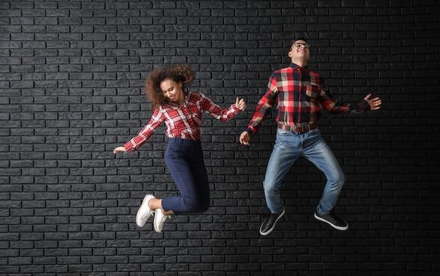 Springendes junges paar gegen dunklen backsteinhintergrund