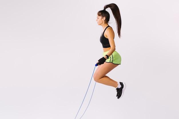 Springendes seil des jungen sportlichen mädchens auf weißem hintergrund mit leerem seitenraum.