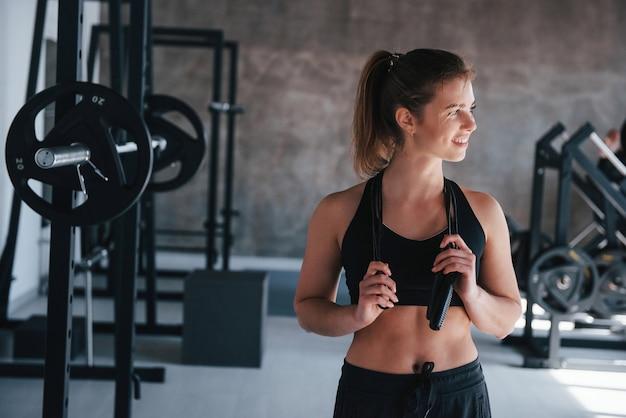 Springseil am hals. wunderschöne blonde frau im fitnessstudio zu ihrer wochenendzeit