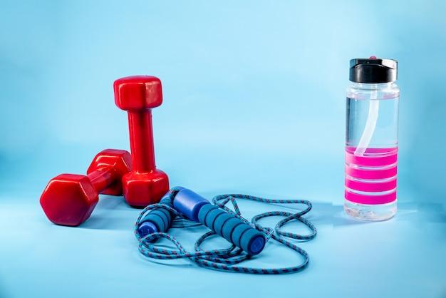 Springseil, hanteln und eine flasche wasser