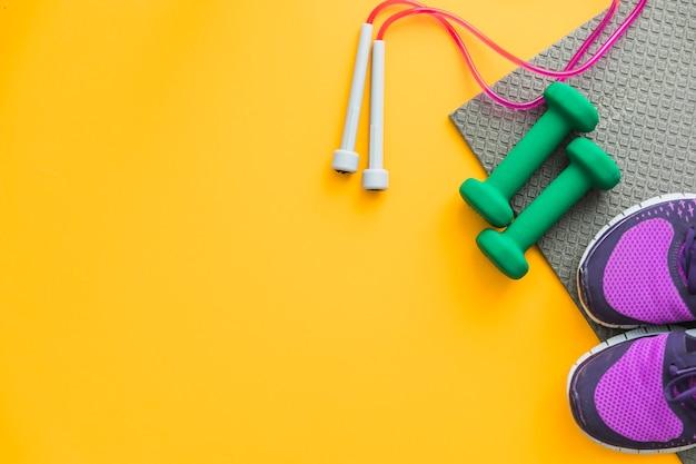 Springseil; hanteln und paar schuhe mit übungsmatte auf gelbem hintergrund