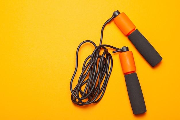 Springseil. lustige übungen für die körpergesundheit. orange seil mit schwarzer schnur. gelber orange hintergrund.