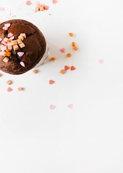 Sprinkle und karamellsüßigkeiten auf schokoladenkleinem kuchen über weißem hintergrund