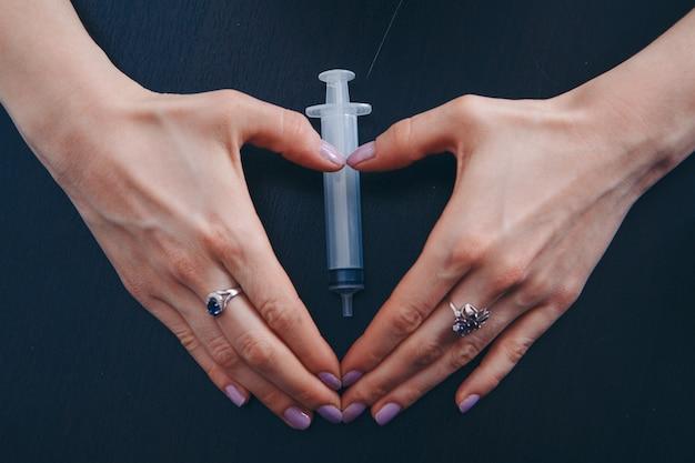 Spritze auf dunkel. hände halten ein medizinisches gerät. eine gesunde lebensweise, gesundheitsversorgung, drogenabhängigkeit, impfung.