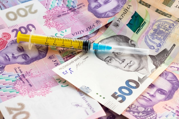 Spritze auf stapel ukrainischer banknoten