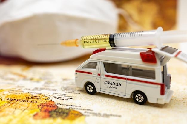 Spritze des covid-19-impfstoffs auf krankenwagen mit medizinischer maske und weltkartenhintergrund. impfstoff und medizinisches konzept für das gesundheitswesen.