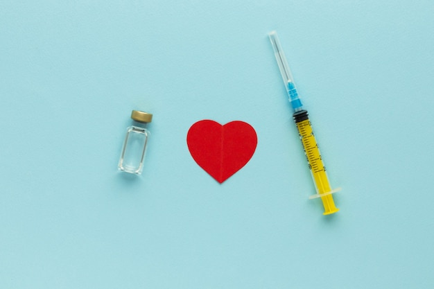 Spritze, glasfläschchen mit flüssigem und rotem papierherz auf blauem hintergrund. impfkonzept für gesundheit und covid-19. medizinische injektion. nadel, dosierungsskala. draufsicht, flach mit kopierraum liegen.