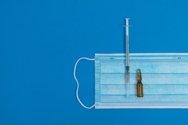 Spritze, maske, ampullen auf blauem hintergrund, impfkonzept.