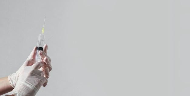 Spritze mit nadel in den händen des arztes auf weißem banner mit kopienraum für text
