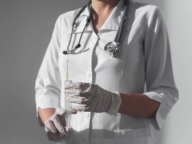 Spritze mit scharfer nadel in ärzten oder krankenschwesterhände in handschuhen