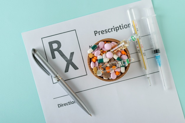Spritze, thermometer, stift und schüssel mit pillen auf einem blatt mit der verordnung eines doktors.