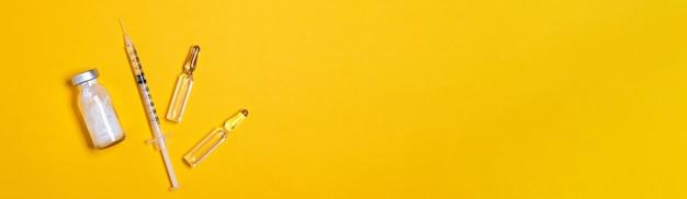 Spritze und impfstoff oder medizinfläschchen auf gelbem hintergrund mit kopienraum für die immunisierung